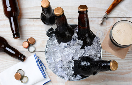 bottle opener: High angle shot of a glass of beer with a metal bucket with unopened bottles. The rustic wood table has empty bottles and caps and an bottle opener. Horizontal Format.