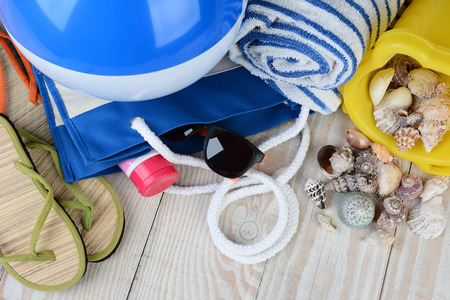 tote: A group of items for a day at the beach, sandals, beach ball, tote bag, sunglasses, towel and sand pail with sea shells, and sun tan lotion. Horizontal format on a wooden deck.