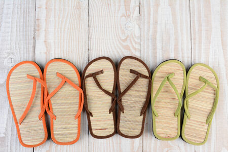 flipflops: High angle shot of a group of summer beach sandals on a wooden deck. The mulit-colored sandals are lined up in a row by pair.