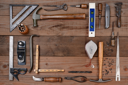 High angle shot of an assortment of contractors well used tools. Horizontal format on a rustic wood background, with a bland space in the middle of the tool arrangement. photo