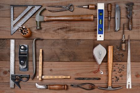 werkzeug: Hohe Winkel gedreht von einem Sortiment von Auftragnehmern und gebrauchten Werkzeug. Querformat auf einem rustikalen Holz Hintergrund, mit einem faden Raum in der Mitte der Werkzeuganordnung.