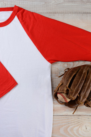 high angle shot: High angle shot of a baseball jersey with a ball and glove on wooden surface.