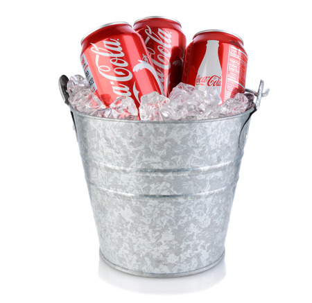 cola: IRVINE, CA - January 09, 2014: Three Coca-Cola cans in an ice bucket. Coke is one of the most popular soft drinks in the world.