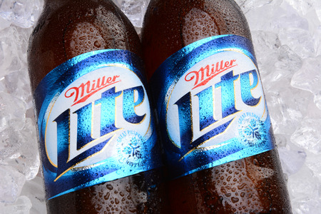 cold: IRVINE, CA - MAY 27, 2014: Two bottles of Miller Light on a bed of ice. Introduced in 1975 Miller Lite was one of the first Reduced Calorie beers to be successful in the American marketplace.