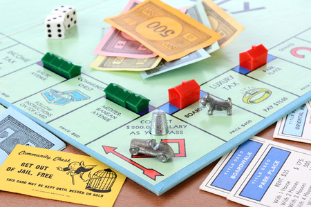 trading board: IRVINE, CA - MAY 19, 2014: Monopoly Board Game Closeup. The classic real estate trading game from Parker Brothers was first introduced to America in 1935.