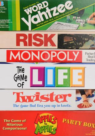 monopolio: IRVINE, CA - 19 de mayo 2014: Una pila de Familia Juegos de Mesa. Los juegos clásicos de Parker Brothers y Milton Baradley, incluyendo Monopoly, Twister, Vida, Riesgo, Yahtzee y manzanas con manzanas.