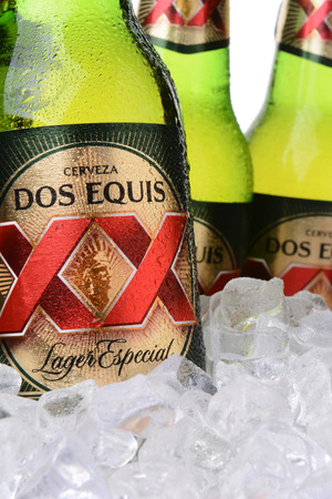 especial: IRVINE, CA - MAY 30, 2014: Closeup of bottles of Dos Equis Lager Especial in ice. Founded in 1890 from the Cuauhtemoc-Moctezuma Brewery in Monterrey, Mexico a subsidiary of Heineken International.