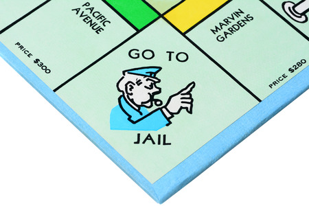 jail: IRVINE, CA - MAY 27, 2014: Monopoly board game closeup of the Go to Jail corner. The classic real estate trading game from Parker Brothers was first introduced to America in 1935.