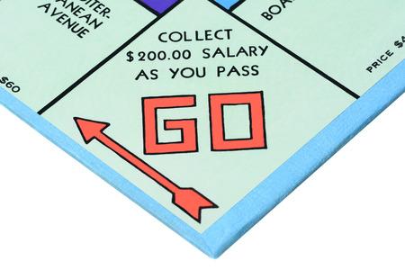 monopolio: IRVINE, CA - 27 de mayo 2014: juego de mesa Monopoly de cerca de la esquina Go. El cl�sico juego de intercambio de bienes ra�ces de Parker Brothers se introdujo por primera vez a Am�rica en 1935.
