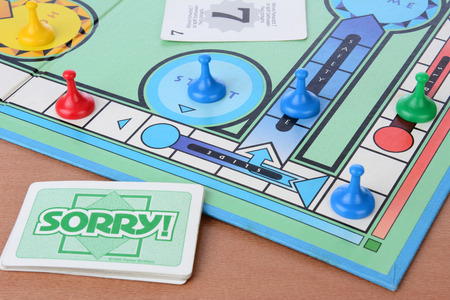 board: IRVINE, CA - MAY 19, 2014: Sorry! board game closeup. Sorry! is a game based on the ancient Cross and Circle game Pachisi. The game is made by Parker Brothers a Division of Hasbro.