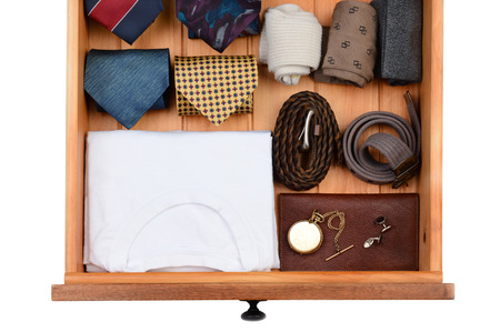 drawers: High angle shot of a dresser drawer with under shirts, belts, neck ties, socks, pocket watch and cuff links. Horizontal format isolated on white.