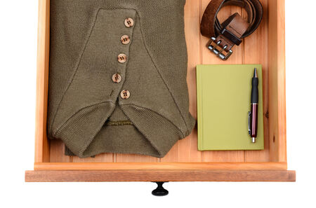 High angle shot of a sweater, belt, book and pen in a dresser drawer. Horizontal format isolated on white. photo