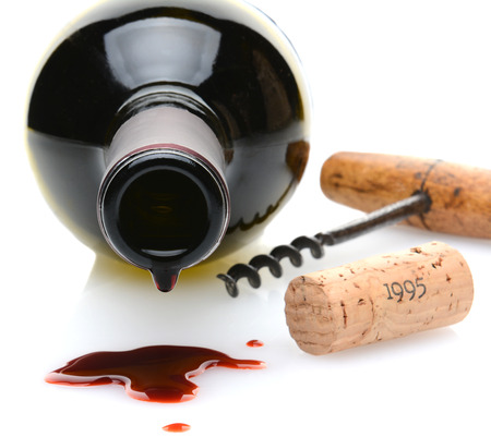 cork screw: Closeup of a red wine bottle with a drip and wine spill in the foreground. A cork screw and cork to one side on a white background with slight reflection. Shallow depth of field with focus on the drip.