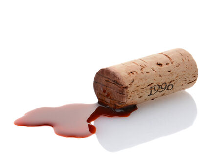 Closeup of a wine cork and a wine spill on white with reflection. Horizontal format.