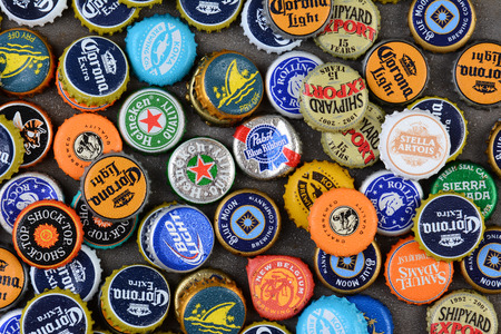 IRVINE, CA - JUNE 16, 2014: High angle shot of a group of assorted beer bottle caps. The caps include both domestic and imported brands.