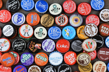 soda bottle: IRVINE, CA - JUNE 16, 2014: High angle shot of a group of assorted soda bottle caps. The caps include Coca-Cola, Crush, Moxie, Sunkist, Fanta, Sprite, IBC, Frostie, Dr. Brown, and Jolt.
