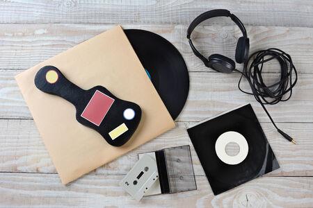 guitar case: Alto �ngulo de disparo de los accesorios de m�sica de estilo retro. Los art�culos incluyen: Vinyl LP, 45 rpm single, auriculares, funda de guitarra y una cinta de cassette. Formato horizontal sobre una superficie de madera blanca.