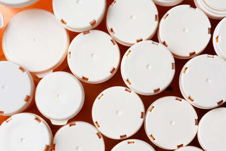 high angle shot: High angle shot of a group of prescription medicine bottles. The tops are blank and are various sizes. Horizontal format filling the frame. Stock Photo
