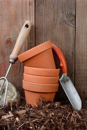 mulch: Closeup of garden tools and flower pots against a wooden backyard fence.