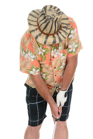 Closeup of an eclecticly dressed male tourist standing over a golf ball preparing to take his turn. He is wearing a Hawaiian shirt, striped shorts and a zebra stripe hat that hides his face.