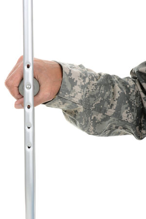 fatigues: Closeup of a soldier holding onto the hand grip of a crutch. Only his hand and arm are visible. The man is wearing camouflage fatigues isolated over white. Stock Photo