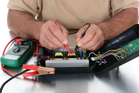 multimeter: Closeup of the hands of a technician testing electrical equipment on his workbench.