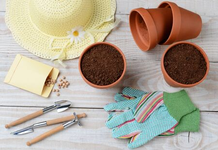 soli: High angle shot of a group of items for potting and planting seeds. Horizontal format on a rustic wooden potting table. Items include, shovel, hat, flower pots, soil, gloves, seed packet and more.