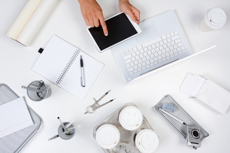 High angle shot of a white desk with primarily white and silver office objects, with a woman holding a tablet computer showing her hands only. Tablet has a blank screen. photo