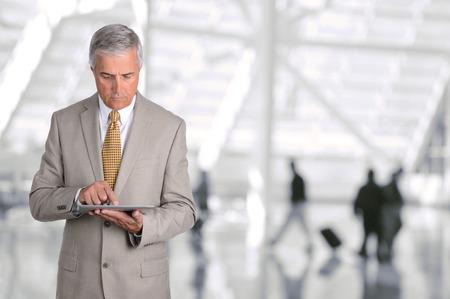 空港コンコースに彼のタブレット コンピューターを使用して成熟した実業家のクローズ アップ。男は、バック グラウンドでぼやけ乗客とデバイス