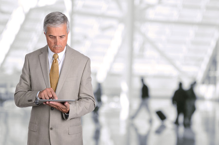 공항 중앙 홀에서 자신의 태블릿 컴퓨터를 사용하는 성숙한 사업가의 근접 촬영입니다. 남자는 백그라운드에서 흐리게 승객 장치를 찾고 있습니다. 스톡 콘텐츠