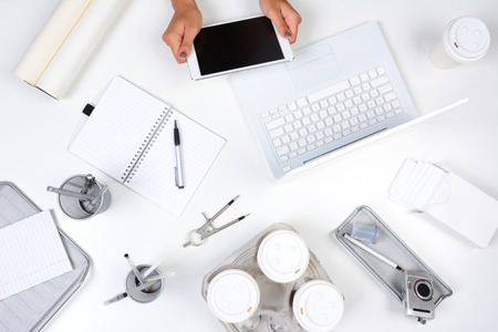 small paper: High angle shot of a white desk with primarily white and silver office objects, with a woman holding a tablet computer showing her hands only. Tablet has a blank screen.