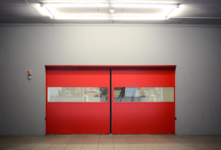 Automatic red warehouse doors. The doors are closed and there is a red light signaling do not enter.  Stok Fotoğraf