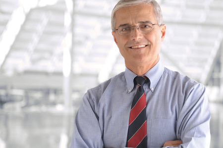 Business man portrait in modern office building. Middle aged man is smiling at the camera and has his arms folded. Closeup head and shoulders only. Standard-Bild