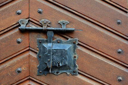 Closeup of an old wooden door with iron lock and latch. Imagens