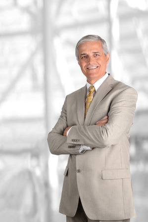 hair tie: A mature businessman with his arms folded against blurred modern office interior. Vertical Format.