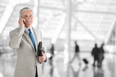 A mature businessman on his cell phone in an airport terminal. The background is blurred with unrecognizable people.