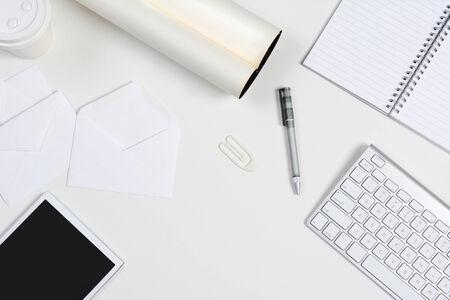 pad pen: Alto �ngulo de disparo de un escritorio blanco puro con la oficina principalmente blanco objetos art�culos incluyen, un equipo Tablet PC, teclado, pad, pluma, taza de caf�, y los sobres con copyspace