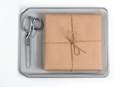 High angle shot of a brown paper wrapped package and scissors in a mesh in-box tray on a white office desk