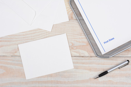 high angle shot: Envelopes and paper for writing letters via snail mail. High angle shot with in-box and pen on a whitewashed desk.