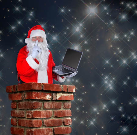 Santa Claus partially inside a chimney with a laptop and making the shh sign with a finger to his lips on a starry night background. photo