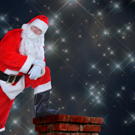 Santa Claus standing on a roof with one foot on the chimney. His arms are folded and he is leaning on his knee against a starry night background with copy space. photo
