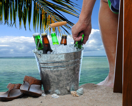 Closeup of a man sitting in a chair at a tropical beach reaching into a bucket filled with ice cold beers. Only the mans leg and are are visible. Stock Photo
