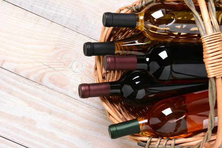 A high angle shot of wine bottles in a basket on a whitewashed wood farmhouse style kitchen table. Horizontal format with copy space. Stock Photo