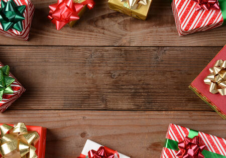 floorboards: A high angle view of a group of Christmas presents on a rustic wooden floor. The presents are scattered around the edges of the frame leaving an empty middle for your object or copy.