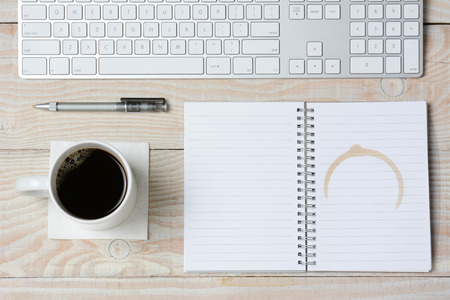 High angle shot of a white rustic desk with a modern keyboard, coffee cup and notebook with a coffee stain. Horizontal format. Stock Photo