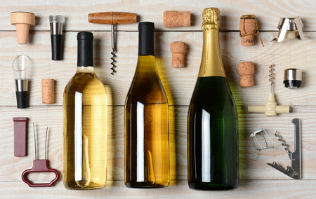 High angle shot of Wine and Champagne bottles surrounded by accessories such as corkscrews,  pourers and corks. Horizontal format on a rustic white wood table. Stockfoto