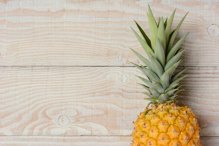 High angle view of a fresh picked pineapple laying on its side on a rustic white wood table. The fruit is golden in color with its green top still attached. Horizontal format.