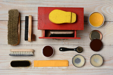old shoes: High angle view of  an antique shoe shine kit and its accessories, including brushes, polish, and buffing cloth. Horizontal format on a white wood surface. Stock Photo