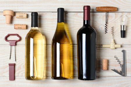 High angle shot of three wine bottles surrounded by accessories such as corkscrews, stoppers, pourers and corks. Horizontal format on a rustic white wood table.