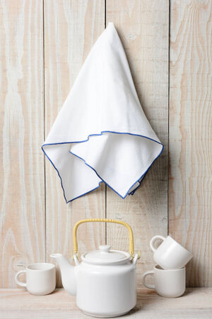 A white tea set on a rustic whitewashed setting with a towl hanging on the wall.
